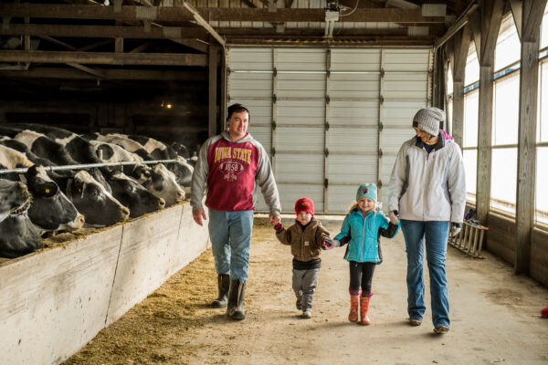 Mom, dad, and two kids walk in their barn with cows to the left.
