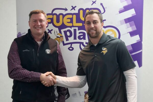 Former Midwest Dairy CEO Lucas Lentsch shaking hands with Minnesota Viking Adam Thielen.