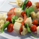 Skewers with pasta, basil, tomatoes, pepperoni, and cubes of cheese.