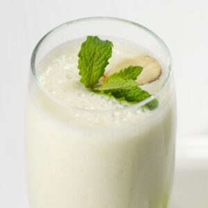 Glass of apple yogurt smoothie garnished with mint and an almond.