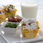 Baked potato cupcakes on a plate with garnishes, with a glass of milk.