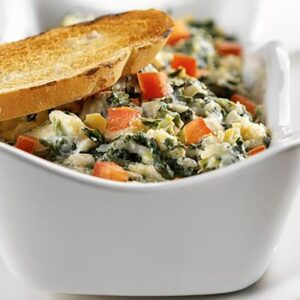 Baked spinach artichoke yogurt dip in atoast-topped dish.