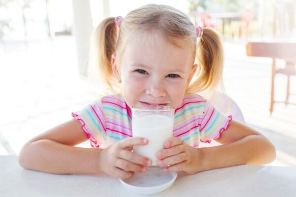 A girl with a glass of milk, seated at a table.