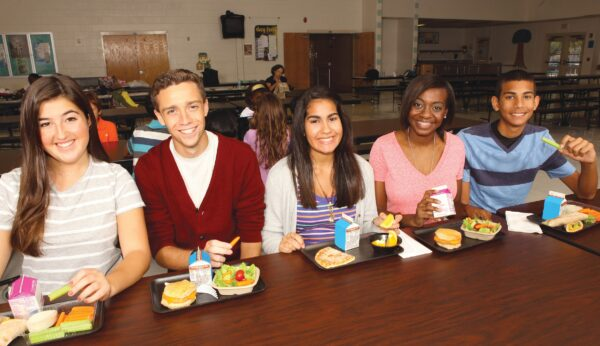 Teens seated at a cafeteria table, enjoying lunch.