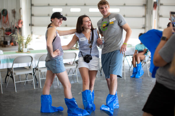 Three teens in blue plastic boots stand in a garage and have their picture taken.