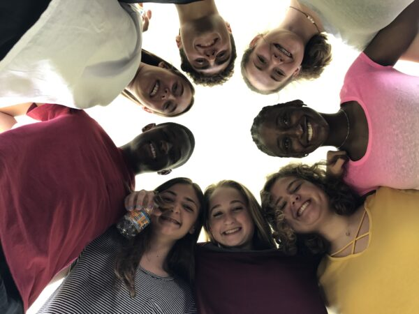 A group of teens form a circle and look down at the camera.