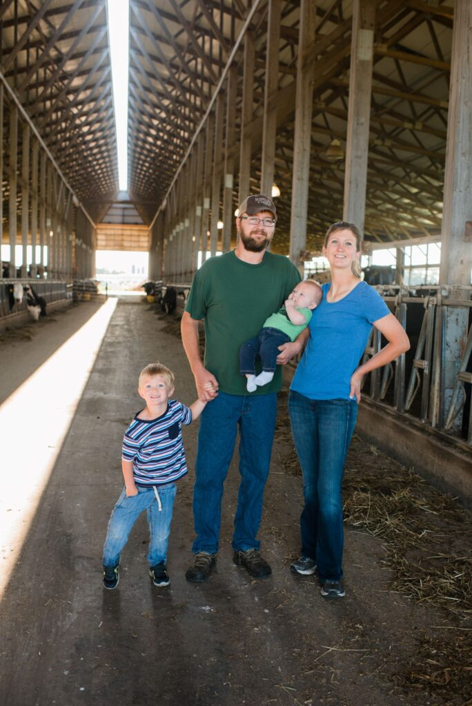 Family with dad, mom and two sons in dairy barn
