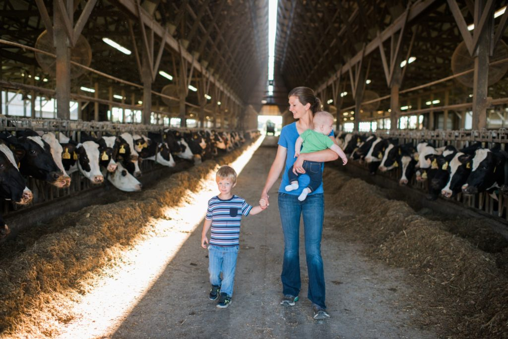 Mom and two sons walking in dairy barn