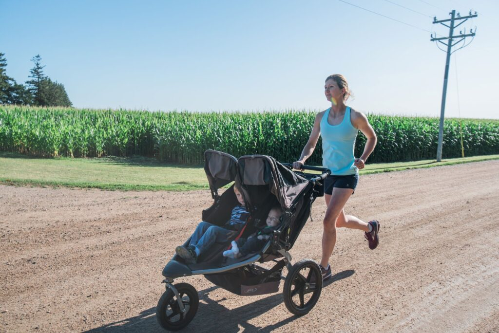 Mom running while pushing a stroller with two boys
