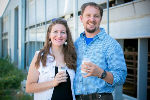 A couple poses in front of a barn, holding glasses of milk.