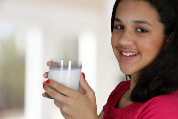 Teenage girl hold a glass of milk.