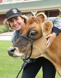 A woman hugs a cow.