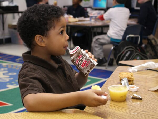 A little boy seated at a table in the school cafeteria, drinking a carton of chocolate milk.