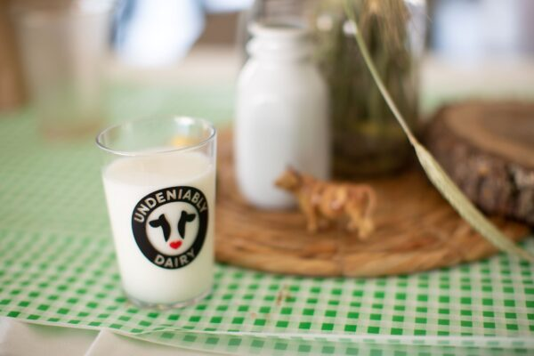 Milk in an Undeniably Dairy glass sits on a table with a bottle of milk, a small cow figurine, and some decorative greenery.
