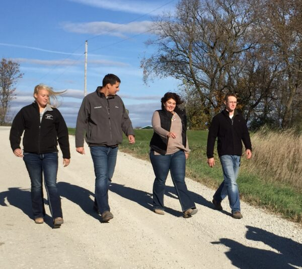 Four young people walk down a gravel road.